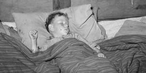 Sick child sleeping in trailer home near Sebastian, Texas. Lee Russell, 1939